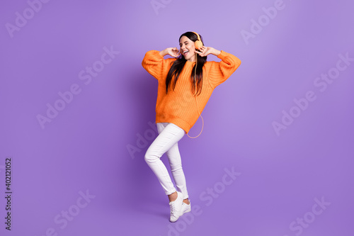 Full size photo of optimistic girl dance listen music wear red sweater trousers sneakers isolated on lilac background