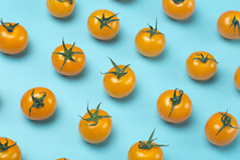 Cherry Tomatoes On A Colored Blue Background. Pattern And Minimal Background Of Yellow Tomatoes