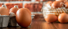 Close-up View Of Raw Chicken Eggs On Wooden Background. Fresh Farm Egg. Eggs In Carton Box. Panorama, Banner