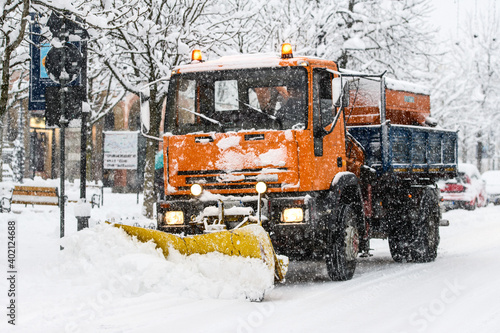 Obraz A snow plow at work during snowfall on whitewashed streets in the city - fototapety do salonu