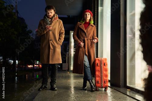 Tela Woman in coat feeling displeased as being neglected by boyfriend
