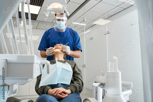 Fotografija Dentist examining teeth of his female blond-haired client
