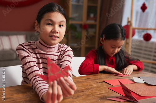 Fotografie, Tablou Little girls spending time together at home sitting at wooden table in living ro