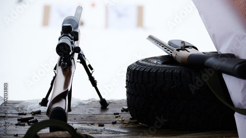 Fotografie, Obraz A sniper rifle and a shotgun lie next to each other against the background of a