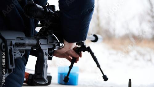 Obraz na plátně A man takes a sniper rifle before shooting sports