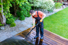 Power Washing - Worker Cleaning Terrace With A Power Washer - High Water Pressure Cleaner On Wooden Terrace Surface