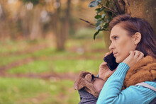 Beautiful Woman Talking On The Smart Phone In Winter In A Park Wearing Coat And Pullover. Carrying Her Child. Maternity Lifestyle