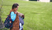 Beautiful Woman In A Park With A Coat And Sweater Carrying A Baby On A Cloudy Winter Day. Maternity Lifestyle Concept