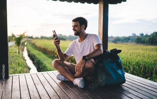 Obraz Cheerful male traveler using cellphone in tropical countryside - fototapety do salonu