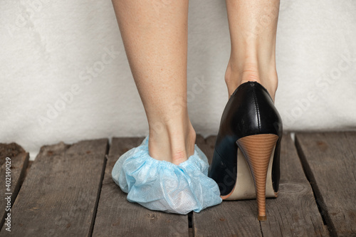 female legs in blue medical protective plastic shoe covers Wallpaper Mural