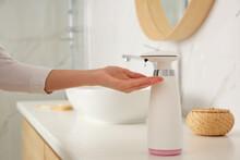 Woman Using Automatic Soap Dispenser In Bathroom, Closeup