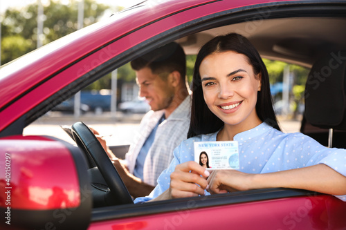 Young woman holding license while sitting in car with instructor. Driving school