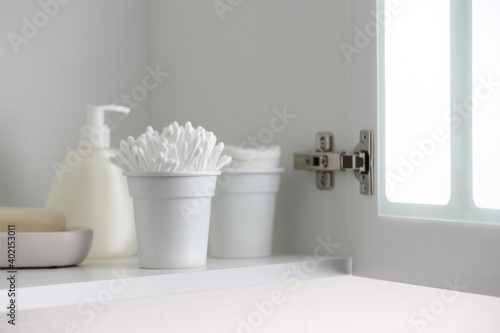 Photo Cotton buds and different toiletries on shelf indoors