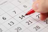 Woman marking Valentine's Day on calendar, closeup