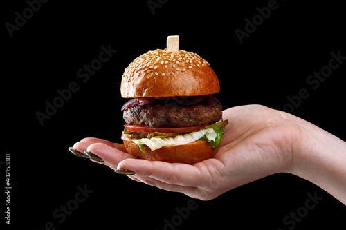 Fototapeta female hand holding mini burger as a Christmas tree toy on black background obraz