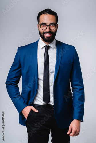 Vertical shot of a handsome middle east man in formal suit isolated over grey background
