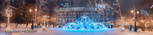 Obraz Wide panoramic view of the illuminated with garlands and twinkling lights fountain in the center of Ufa, Russia. Christmas and New Year decorations and holidays. - fototapety do salonu