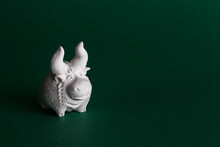 Ceramic Figurine Of A White Bull On A Green Background. The Bull Is The Symbol Of 2021.