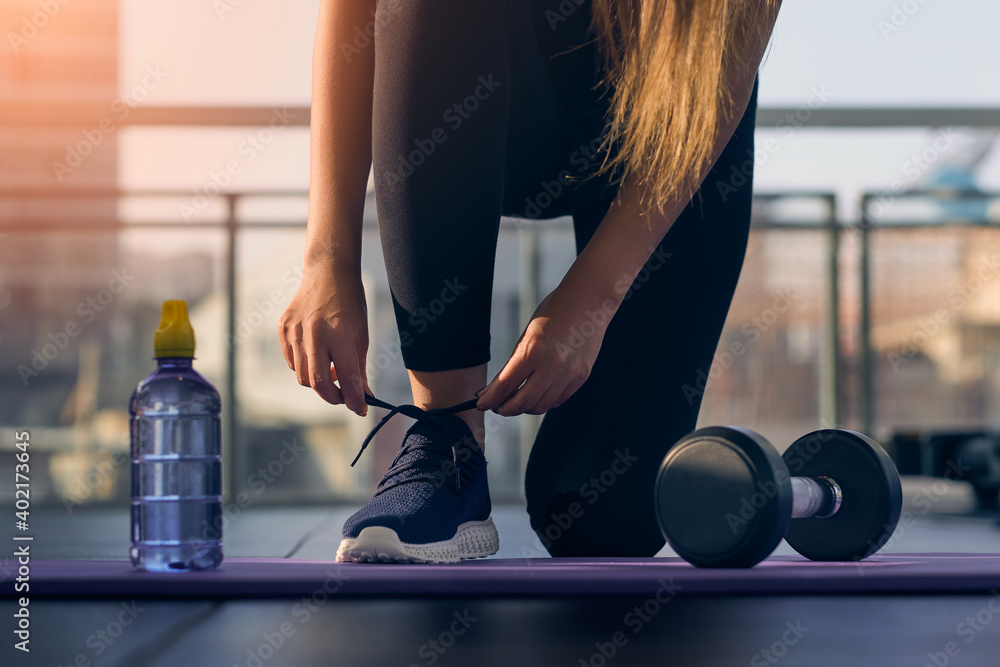Fototapeta Woman tying sneaker shoelaces in fitness gym . Sportswoman starting exercise with dumbbell weight . Sport motivation concept .