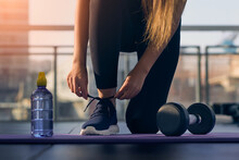 Woman Tying Sneaker Shoelaces In Fitness Gym . Sportswoman Starting Exercise With Dumbbell Weight . Sport Motivation Concept .