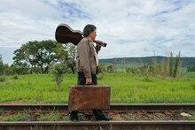 Senior Man Walking Along The Railroad Carrying A Guitar And A Suitcase