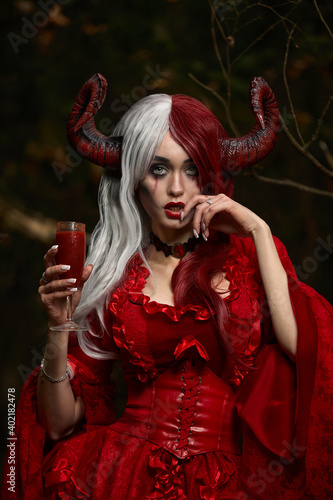 Obraz na plátně Maleficent Woman in Red Clothing and Horns in dark Forest