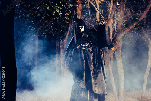 Photo Portrait of the angel of death, grim reaper while standing in a mystical wood at night