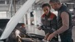 Slowmo handheld shot of black female auto mechanic in uniform holding clipboard and pointing out problem under hood of car while talking to client in workshop