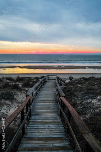 Fototapeta Atardecer en la playa de invierno nubes arena reflejos sur de españa con junco