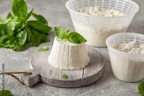 Fotografija Homemade whey ricotta cheese or cottage cheese with basil ready to eat