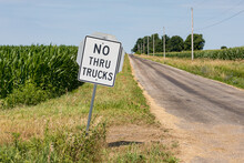 No Thru Trucks Road Sign Along Rural Asphalt Road. Concept Of Transportation, Trucking, Farming, And Road Damage