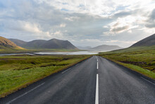 Deserted Mountain Road Sloping Down Toward The Sea In Iceland On A Cloudy Summer Evening