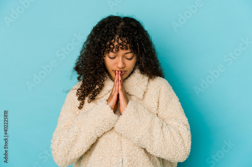 Fotografie, Obraz Young african american afro woman isolated praying, showing devotion, religious person looking for divine inspiration