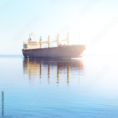 Photo General cargo ship with cranes sailing in a still sea water