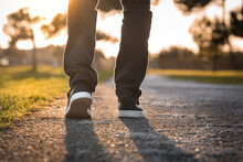 Man Walking Outdoors In The Park At Sunset. Closeup On Shoe, Taking A Step.