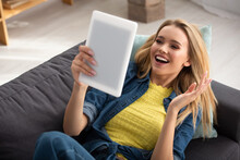 Blonde Woman With Waving Hand Looking At Digital Tablet While Lying On Couch On Blurred Background