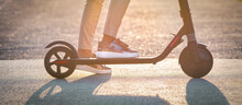 Close Up Of Stylish Woman Riding Electric Kick Scooter At Sunset. Electric Eco Transportation