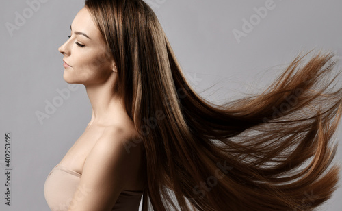 Profile of young sensual woman wearing tight top bra standing with closed of pleasure eyes and long silky straight hair flying fluttering in the wind over grey background. Haircare, beauty, wellness