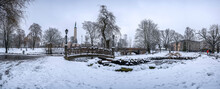 Panoramic Winter Landscape In Snowy Park With Beautiful Bridge Over Small Pond, Street Light And Covered In Snow Tress. View Of Bastion Hill Park And The Freedom Monument In Riga, Latvia