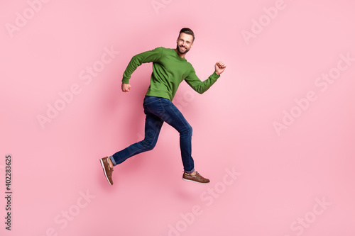 Obraz Full length body size profile side view of attractive cheerful guy jumping running fast isolated over pink pastel color background - fototapety do salonu