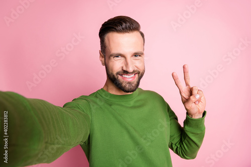 Self-portrait of nice cheerful mature guy showing v-sign good mood isolated over pink pastel color background