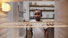 Hungry Poor Little African Girl Look For Food In Empty Fridge At Home.