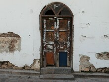 Antalya, Turkey, October 24, 2020: A Weather And Peeling Wooden Door Hangs Crookedly In Its Arched Frame Set In A Crumbling, White Stone Wall.