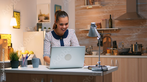Fototapeta Excited woman feel ecstatic reading great online news on laptop working from home kitchen