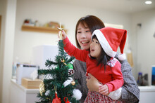 クリスマスツリーの飾りをつける親子