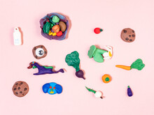 Various Hand-crafted Figurines From Polymer Clay On Pink Paper Background