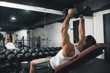 A Man In White Tank Top Does Some Incline Dumbbell Flys. Working Out, Training Chest With An Isolation Exercise.