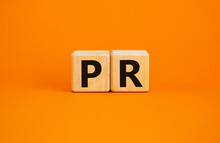 PR - Public Relations Symbol. Wooden Cubes With Words 'PR, Public Relations' On Beautiful Orange Background, Copy Space. Business And PR - Public Relations Concept.
