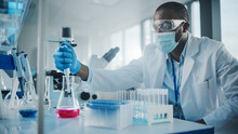 Medical Development Laboratory: Black Scientist Wearing Face Mask Uses Pipette For Filling Test Tube With Liquid, Conducting Experiment. Pharmaceutical Lab With Medicine, Biotechnology Researchers