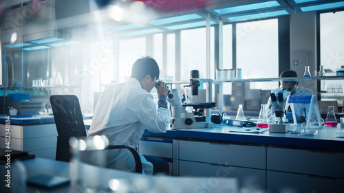 Fotografija Medical Development Laboratory: Scientist Looking Under Microscope, Analyzes Petri Dish Sample